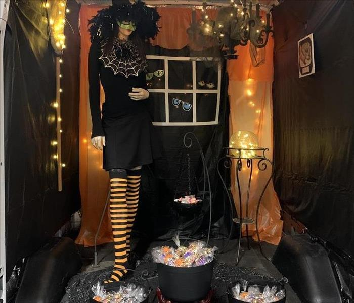 Back of a truck. With lights strung, a mannequin dressed up as a witch and candy in plastic cauldron